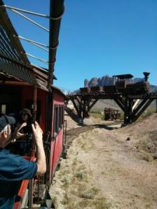 Riding a train with the Superstitions behind us going under a bridge.