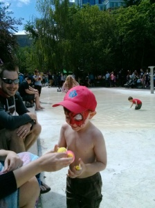 Jackson with his face painted playing the splash pool.